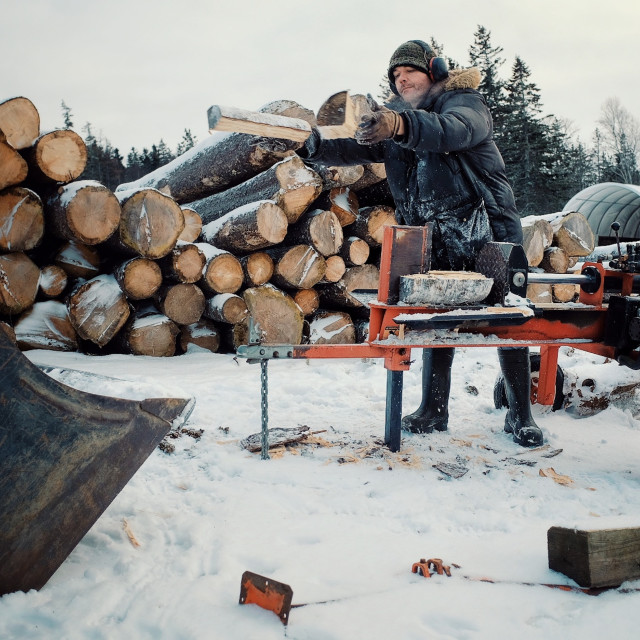 """""""local farmer man chopping and cutting fire wood for heating during the cold winter months in a snow hail storm"""" stock image"""