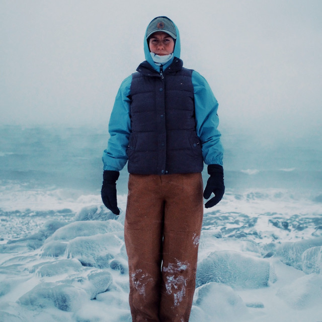 """""""young explorer nomad lifestyle girl in arctic nordic freezing conditions in front of the stormy raging sea covered with ice and snow"""" stock image"""