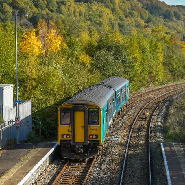 """Diesel commuter train departing from a platform"" stock image"