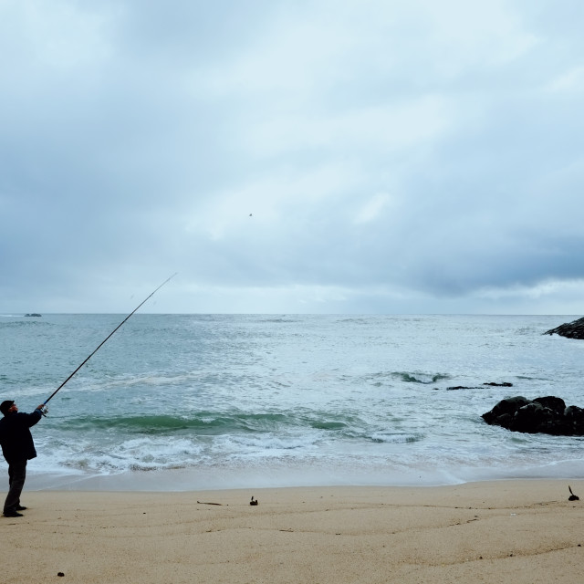 """""""local fisherman angler casting his lure at a sandy shore beach on the atlantic ocean"""" stock image"""