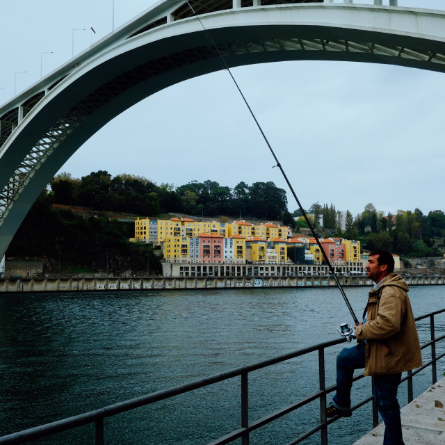 """""""local man fishing next to one of the most iconic bridge of the city with colorful buildings in the background"""" stock image"""