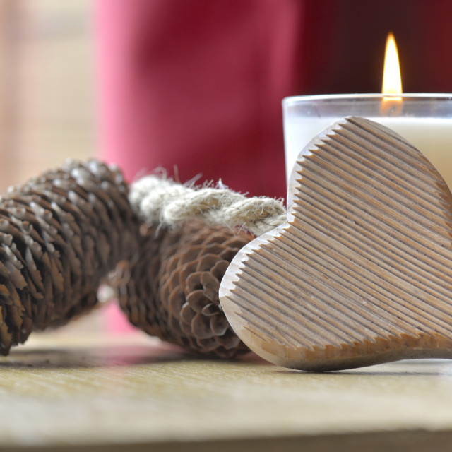 """heart against a candle with pine cones put on a table"" stock image"
