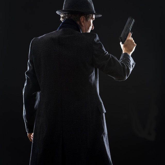 """""""silhouette of a man with a gun wearing a coat and trilby"""" stock image"""