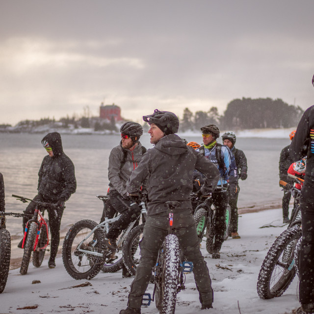 """A group of fatbikers gather for a snowey beach ride."" stock image"