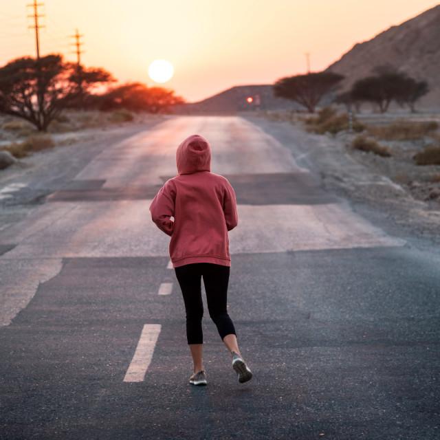 """""""Girl running in sunset wearing pink hoody"""" stock image"""