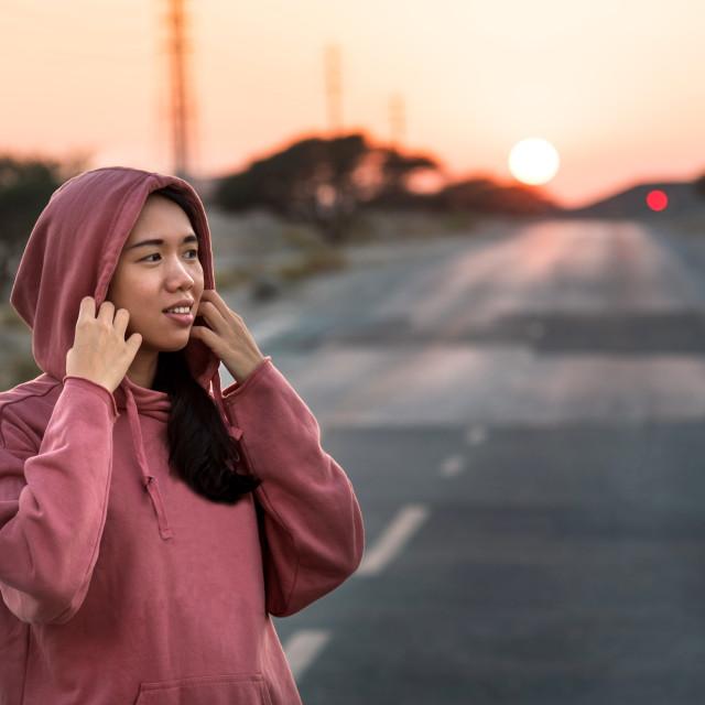 """Fashionable runner wearing pink hoody at sunset"" stock image"