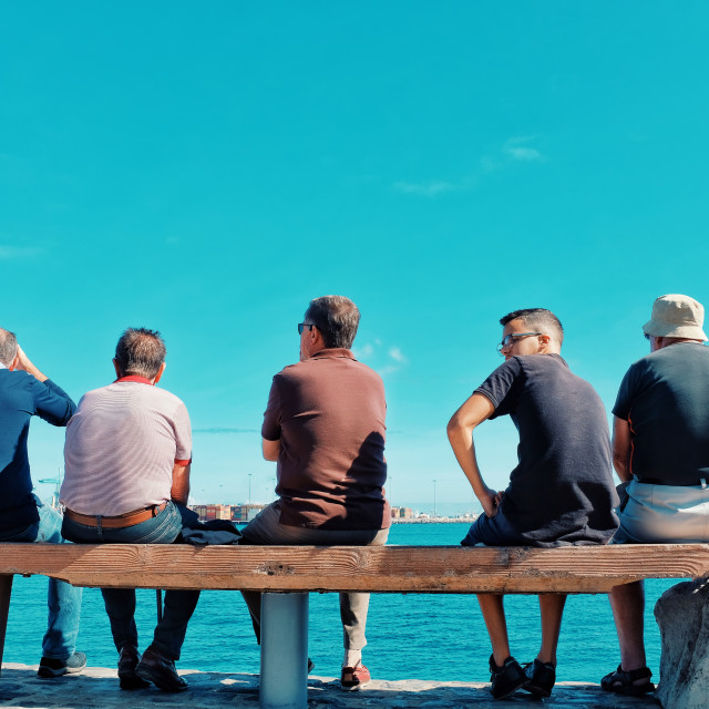 """""""spectators crowd people sitting on a bench to watch the atlantic ocean crossing sail boat regatta race ARC 2018"""" stock image"""