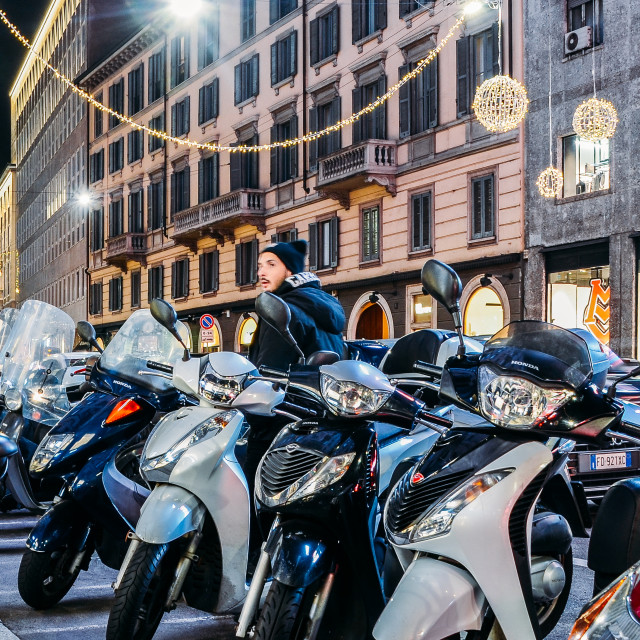 """Rows of parked motor scooters in Milan at night. Vespas are an iconic Italian..."" stock image"