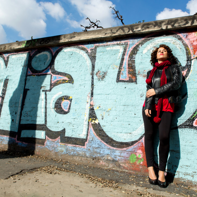"""Beautiful woman posing with blue graffiti"" stock image"