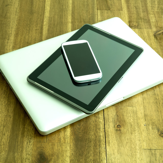 """Digital devices on a wooden Desktop"" stock image"