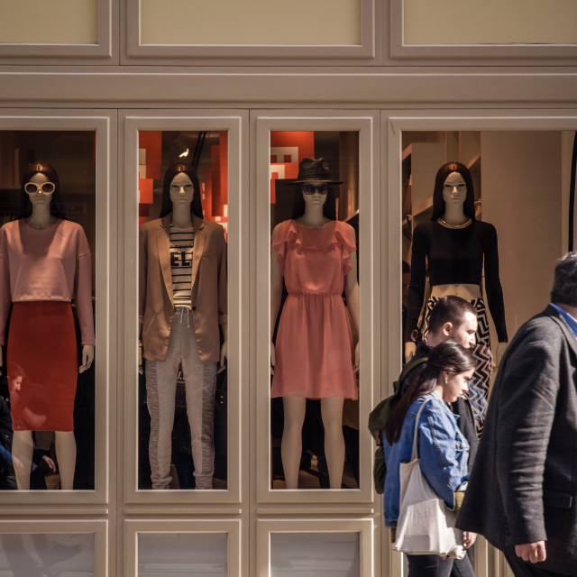 """Tourists Passing by Women Clothing Store Window"" stock image"