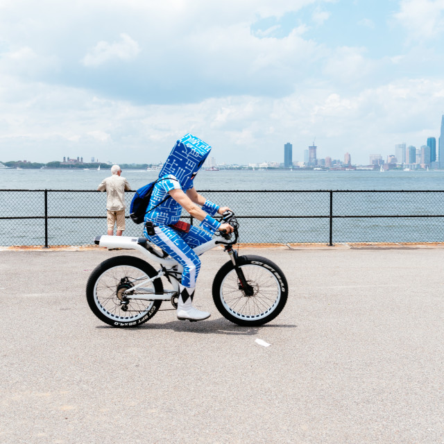 """Man riding a bicycle along promenade in New York City"" stock image"