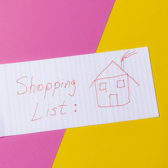 """""""Real estate shopping list on a yellow and pink desk. Buying a house concept."""" stock image"""