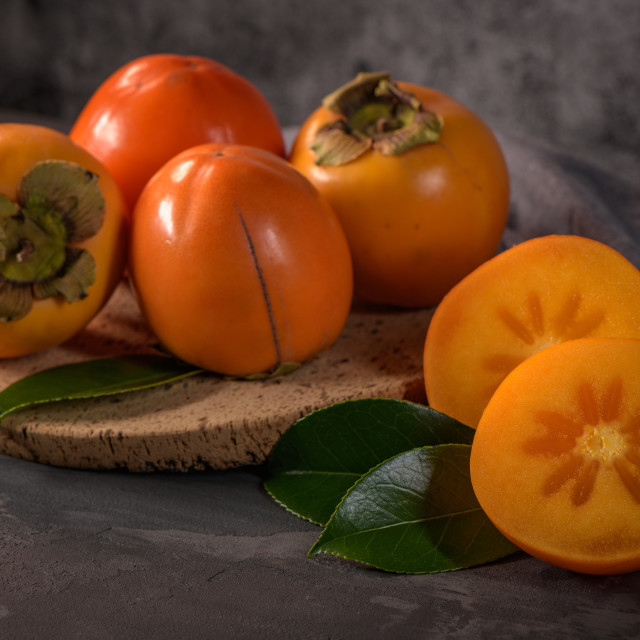"""""""Ripe persimmon fruits in a cork plate"""" stock image"""