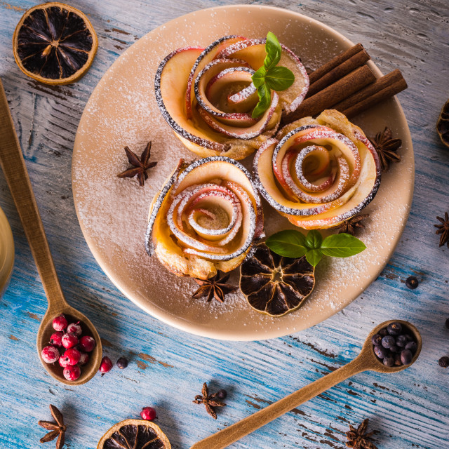 """Crispy apple roses on color plate with several herbs and spices"" stock image"