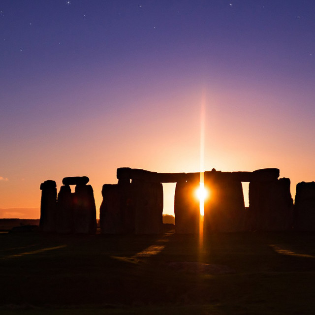 """The sun drops behind Stonehenge"" stock image"