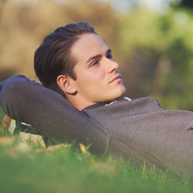 """""""Soccer Player Lying in the Grass with Football"""" stock image"""