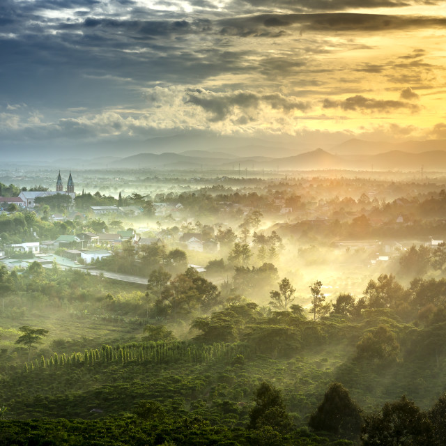 """Sun rays at the valley on Bao Loc town. The far side is Thanh Xa Church in Lam Dong province, Vietnam."" stock image"