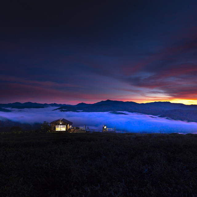 """""""Small house located in the edge of the valley with full of the clouds in the early morning, when the sun is rising."""" stock image"""