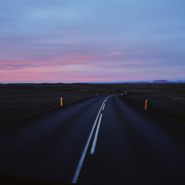 """Driving an empty Iceland road at sunset."" stock image"