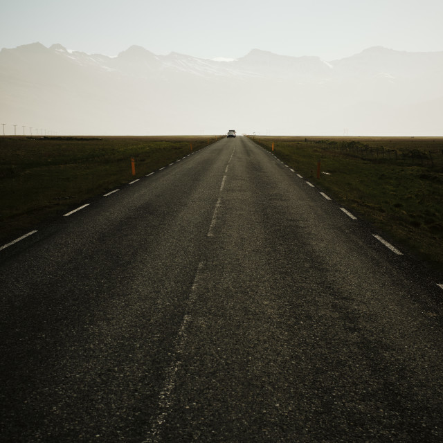 """""""A straight road and distant oncoming traffic and mountain range"""" stock image"""