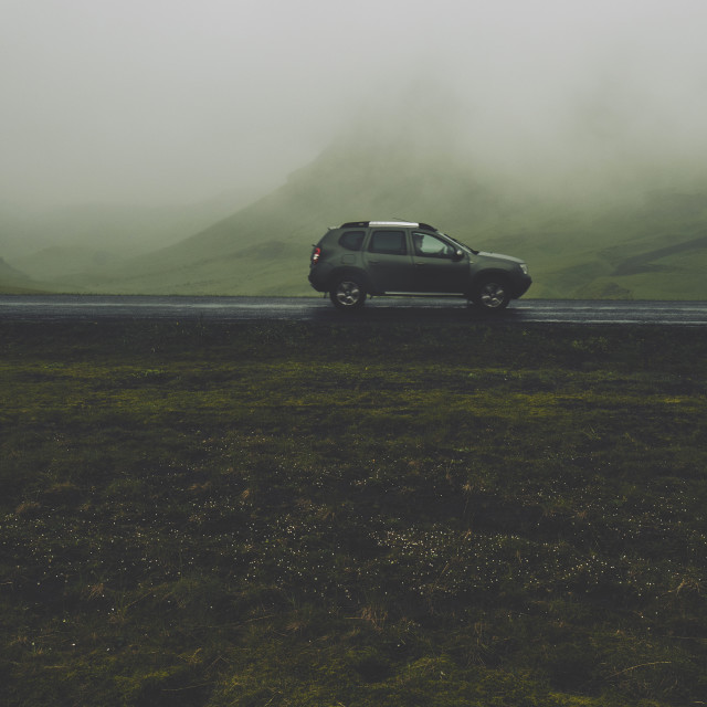 """""""A lone car traveling in a low cloud mountain landscape."""" stock image"""