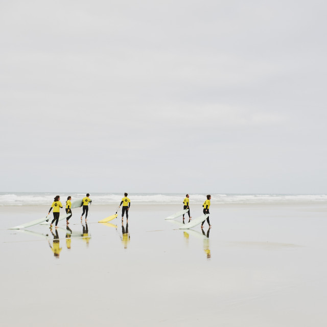 """Surf school students on an empty sandy beach."" stock image"