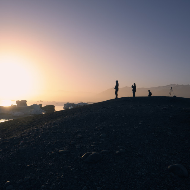 """Photographer silhouettes in the midnight Icelandic landscape."" stock image"