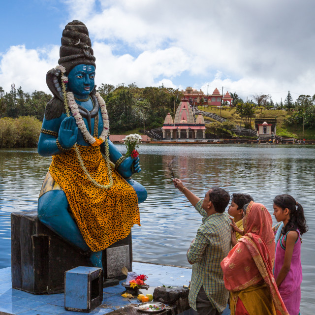 """Family offering prayer to Lord Shiva at temple by the holy lake"" stock image"