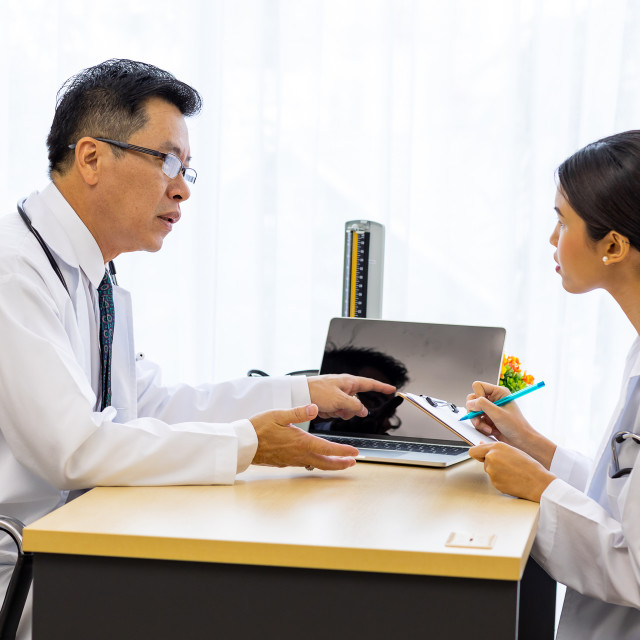 """Two doctors in the hospital discuss the diagnos of the patient"" stock image"