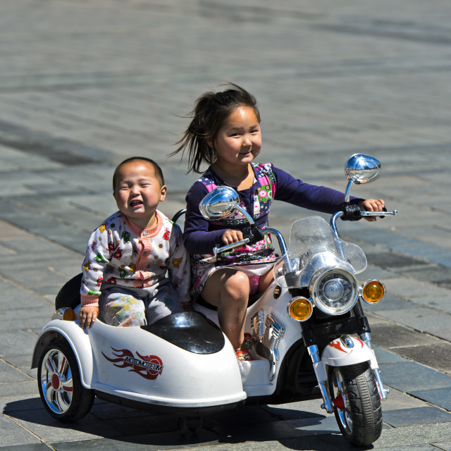 """6 to 8-year old girl riding an electric toy motor-bike with her brother on..."" stock image"
