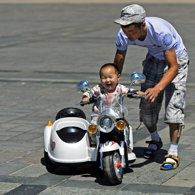 """Toddler boy riding an electric toy motor-bike with the help of his fahter on..."" stock image"