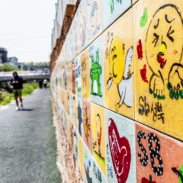 """Graffiti on the banks of a stream in Seoul"" stock image"