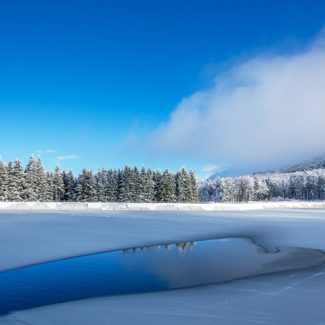 """Blue ice and cracks on the surface of the ice. Frozen lake under"" stock image"