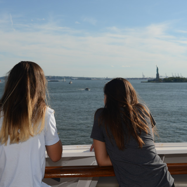 """Girls watching the Statue of Liberty from Ship"" stock image"