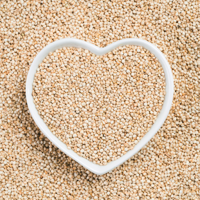 """Quinoa in heart-shaped bowl on quinoa background"" stock image"
