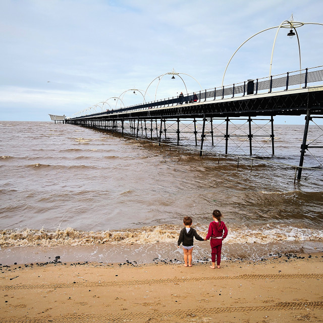 """Beach scene of children holding hands, Southport Pier"" stock image"