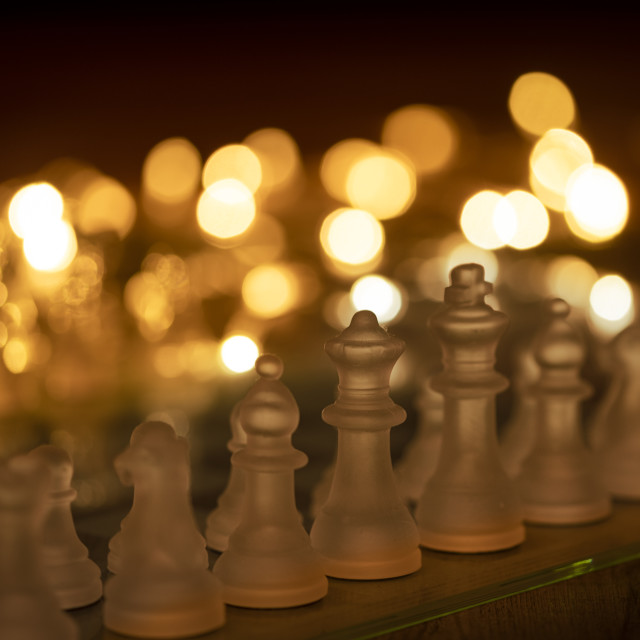 """""""close up of a glass chess set with warm lights in the background"""" stock image"""