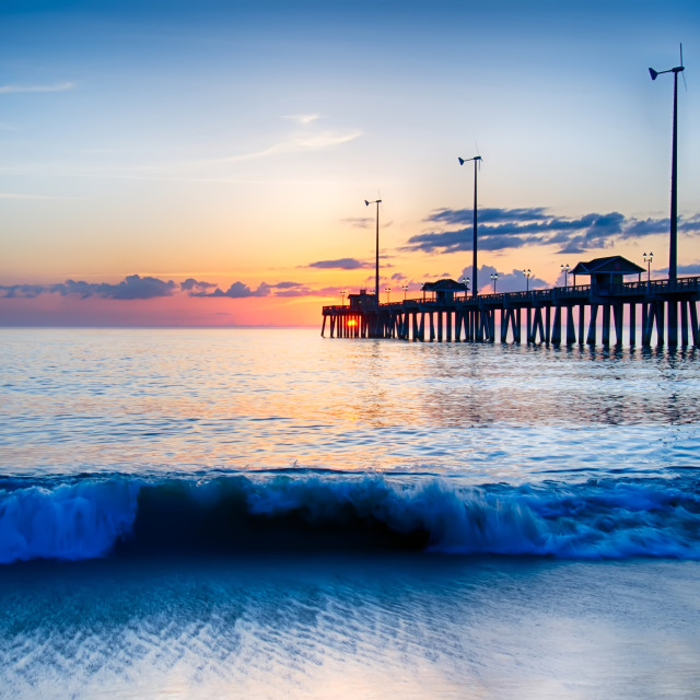 """""""The rising sun peeks through clouds and is reflected in waves by the Nags..."""" stock image"""