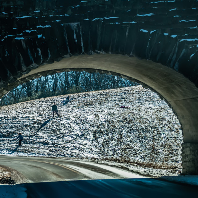 """snow sledding down the hill seen under the bridge tunnel"" stock image"