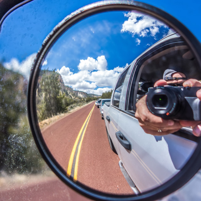 """""""camera reflected in the rearview mirror of a car on a summer day"""" stock image"""