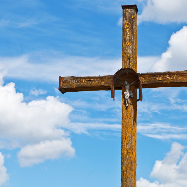 """""""Figurine of Jesus Christ on a wooden cross against under blue cloudy sky, Poland, Europe"""" stock image"""