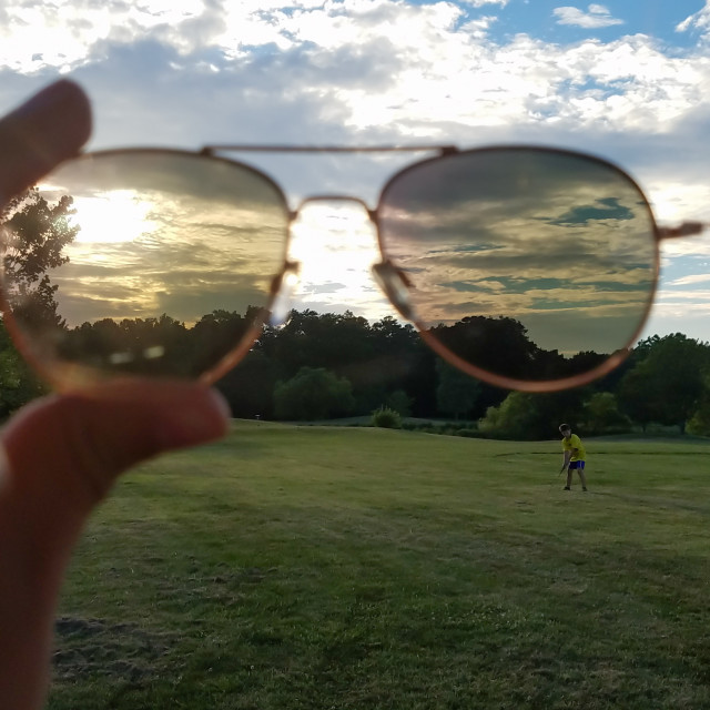 """Watching golfer and sunset through sunglasses"" stock image"