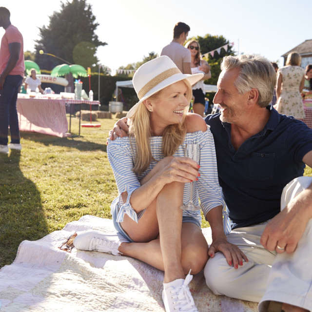 """Mature Couple Sitting On Rug At Summer Garden Fete"" stock image"