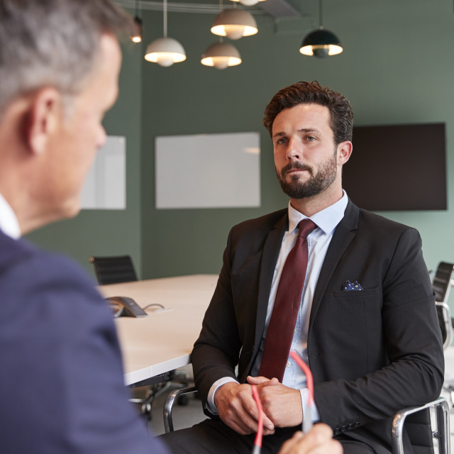 """Businessman Interviewing Male Candidate At Graduate Recruitment Assessment..."" stock image"