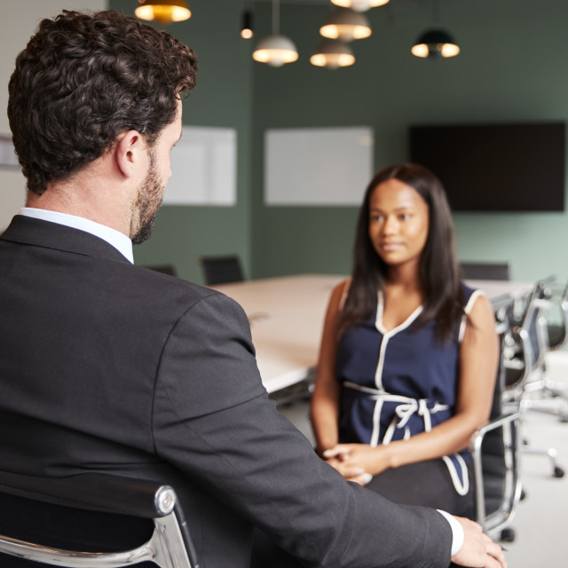 """Businessman Interviewing Female Candidate At Graduate Recruitment Assessment..."" stock image"