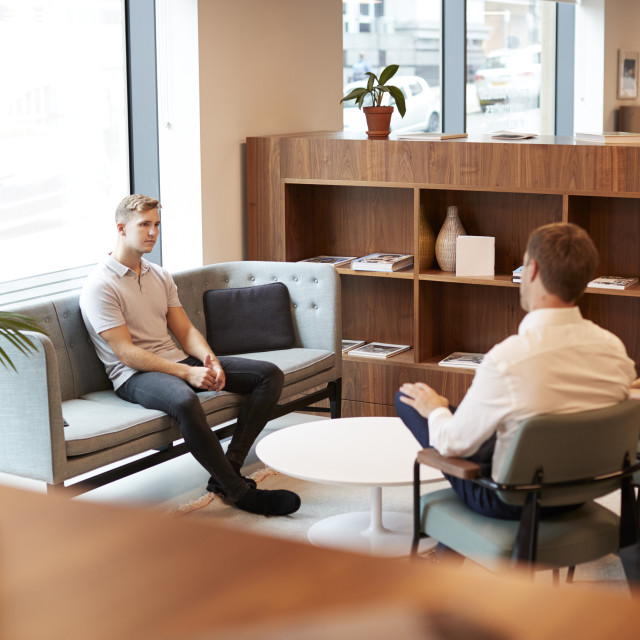"""Businessman And Businesswoman Interviewing Male Candidate In Office At..."" stock image"
