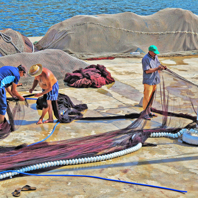 """Fishermen mending nets in Spain"" stock image"