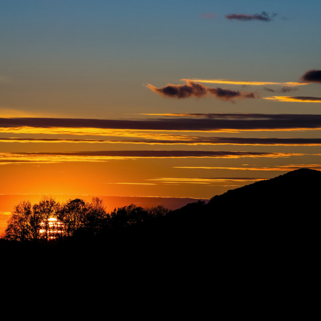 """""""Silhouetted hill and trees during a glowing sunset; Waterloo, Quebec, Canada"""" stock image"""