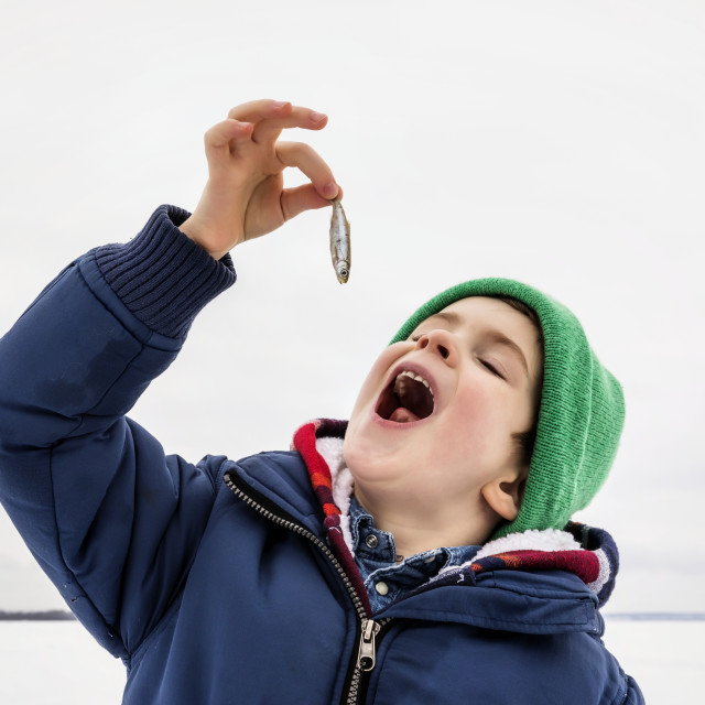 """""""Young boy pretending to eat a baitfish minnow while ice fishing at Wabamun..."""" stock image"""